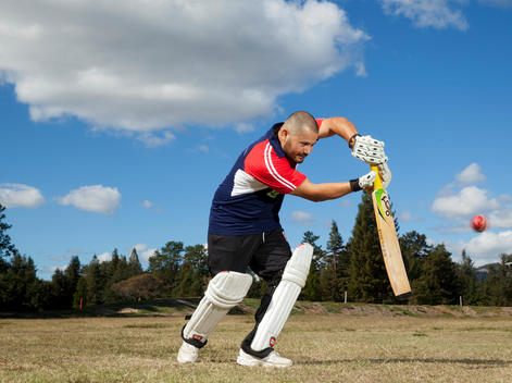 A cricket player swings his bat on the field