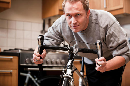 Mid Adult Man Holding Bicycle At Home