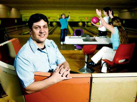 Portrait Of Father In Bowling Alley, Family Celebrating Strike