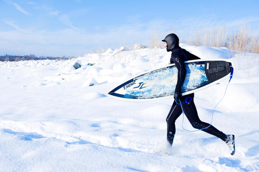 Man with surfboard walking through snow