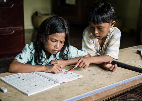 A boy helps a girl with her schoolwork at The Wat Opot Community, an orphanage for children affected by HIV and AIDS, near Chambak, Cambodia, outside Phnom Penh.