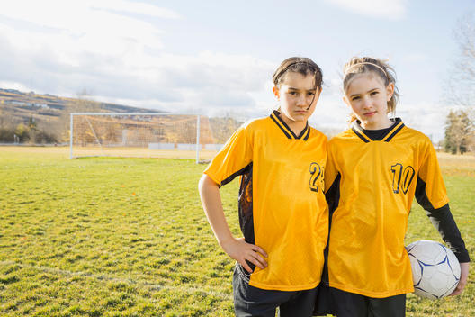 Portrait of confident soccer players on field