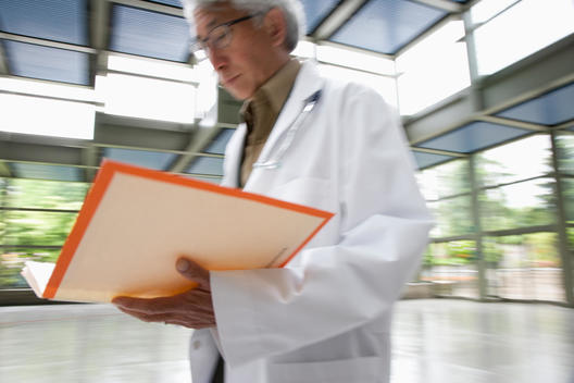 Asian doctor walking and looking at medical record
