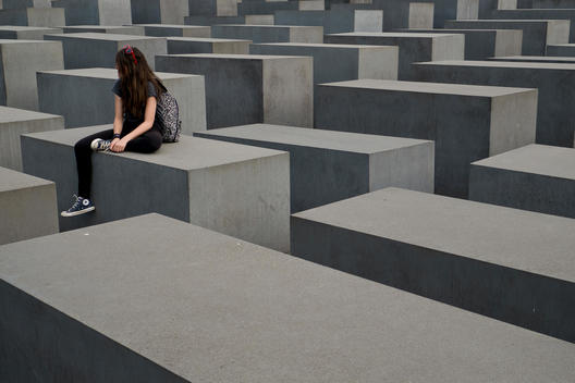 The Holocaust Memorial designed by the architect Peter Eisenman. A girl sitting on one of the grey concrete steal blocks.