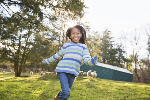 A young girl in a blue stripy top running in a field of sheep at an animal sanctuary.