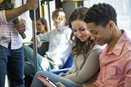 Urban Lifestyle. A group of people, men and women on a city bus, in New York city. A couple side by side looking at a digital tablet.