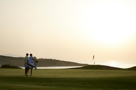 Men on golf course at sunset