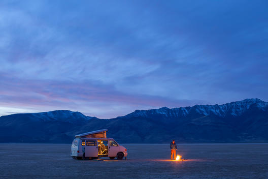 A man standing by a campfire near a camper van on a wide expanse of a valley.