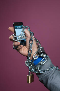 A man\'s hand holding an iPhone has chains and locks wrapped around it