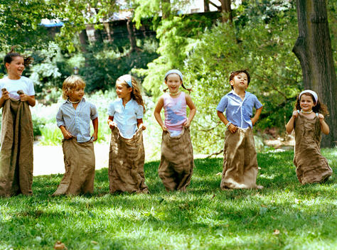 A Group Of Children Having A Potato Sack Race.