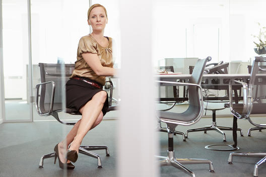 Businesswoman sitting in office chair at conference table