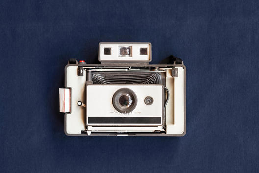 Top view of old instant camera on blue table