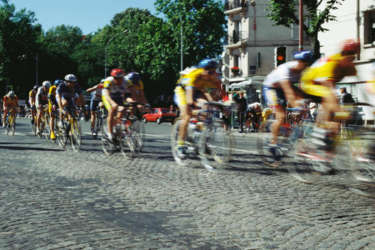 Cyclists racing on cobblestone street