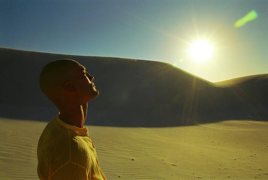 Man In Desert Enjoying Sun On His Face