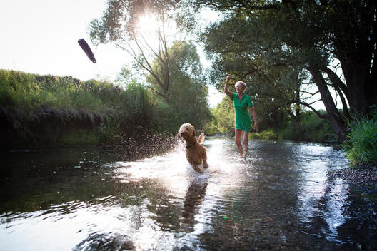 Senior woman playing with her dog in water