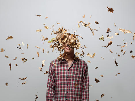 Young man with face obscured by leaves