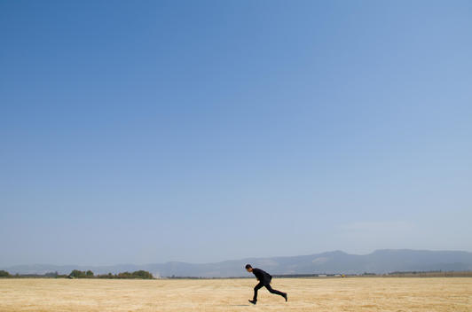 Man In Business Attire Sprinting Across Field