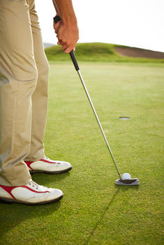 Man preparing to putt on golf course