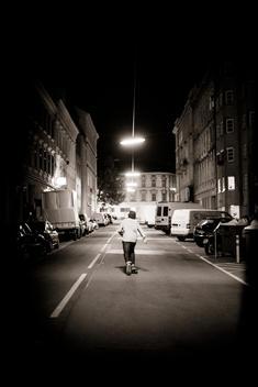 Man pushing a skateboard down a European street at night.