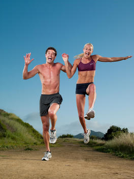 An athletic man and woman jump up in unison on a hiking trail