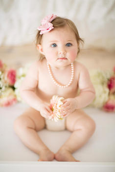 Baby girl in diaper, sitting among roses, holding pink flower, wearing pink pearls and bow.