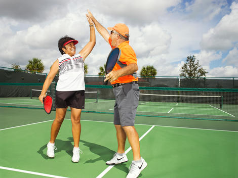 A retired couple high five on a tennis court after a win