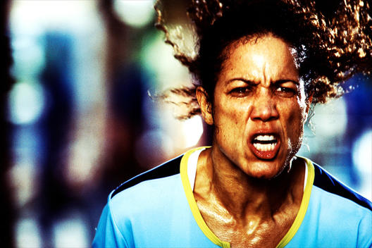 Tight Shot Of An African American Female Wearing A Light Blue Athletic Shirt With A Grimace On Her Face.