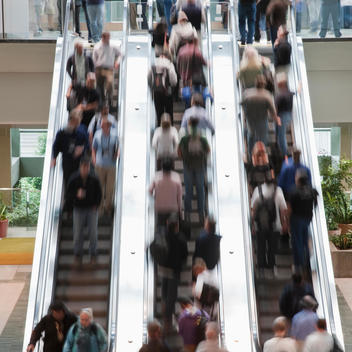 Busy people standing on escalator