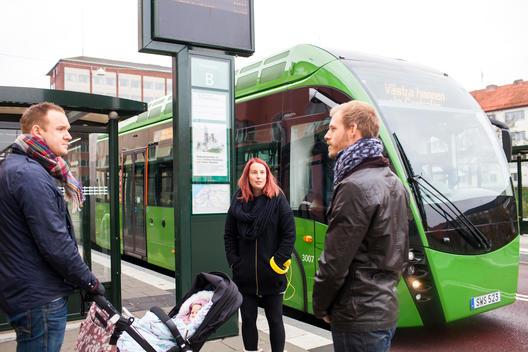 People conversing at bus stop