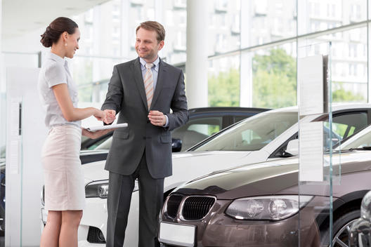 At the car dealer, Smiling salesman talking to client