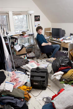 Man Distracted From Work By Watching Tv In His Messy Home Office