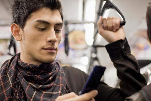 Close up of mixed race man text messaging with cell phone on subway