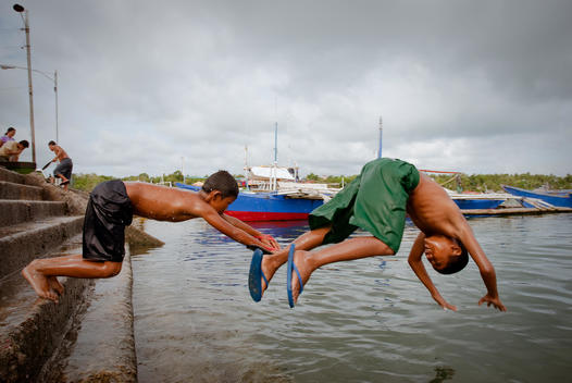 Children Diving Into Water From Harbor