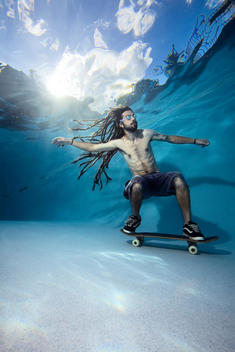 Man skateboarding under water