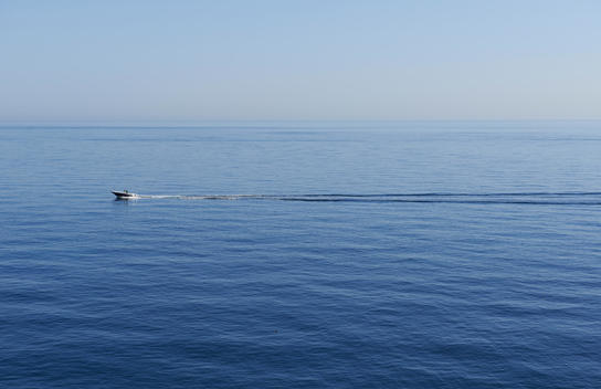 a speedboat ripping up the calm sea water near Polignano a Mare