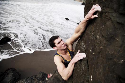 An athletic man rock climbing at the beach