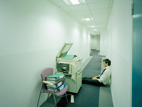 Man sitting in corridor fed up with work