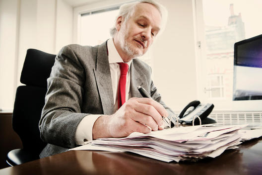 Senior businessman at desk with paperwork