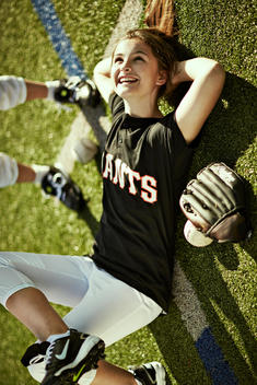 Portrait of girl softball player laying in turf