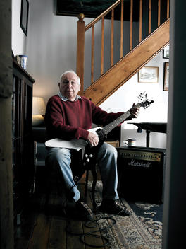 Senior Man Playing Electric Guitar In His Living Room.