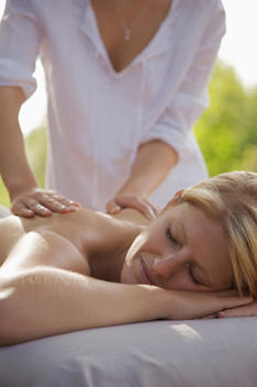 Young woman receiving a back massage outside