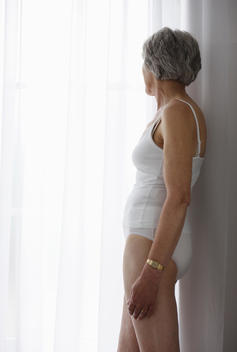 Senior Woman Standing In White Underwear At Window