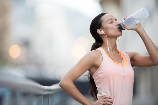 Woman drinking water after exercising on city street