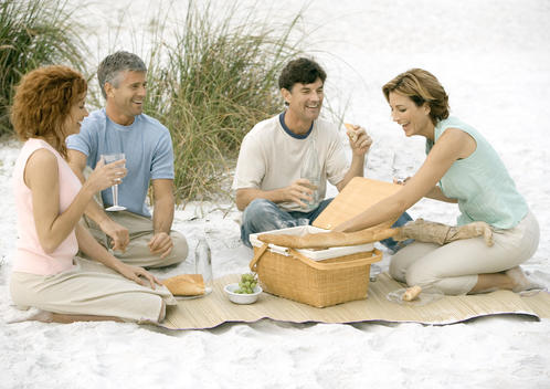 Two mature couples having picnic on beach