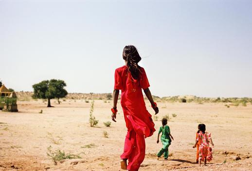 exterior shot of four young Indian women walking through dessert