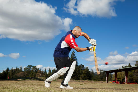 A cricket player swings at the oncoming ball in a game