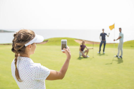 Woman photographing friends on golf course