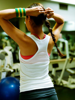 Athletic Girl In White Tank Top In Gym Playing With Her Braid