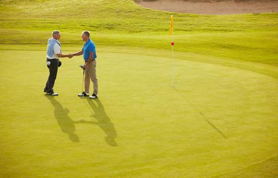 Senior men shaking hands on golf course