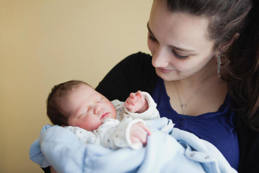Teenage girl holding newborn baby